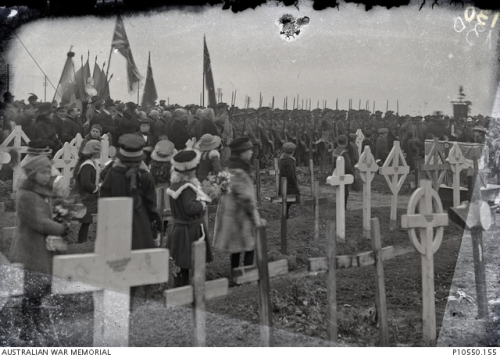 17 November 1918 Australian soldiers, along with children and townspeople, gather in the Vignacourt cemetery for a commemoration ceremony led by the Mayor of Vignacourt to hand over the care of the graves to the local children.